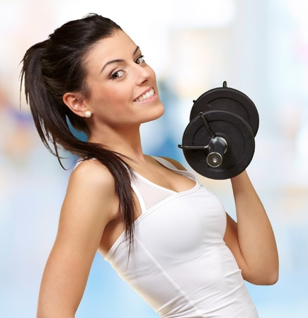 weight room: portrait of a young pretty woman holding weights and doing fitness indoor