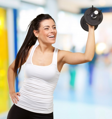portrait of young girl training with weights at gym photo