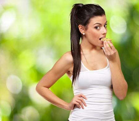 barre de c�r�ales: jeune fille en bonne sant� de manger une barre de c�r�ales contre un fond de nature