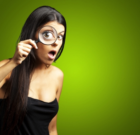 portrait of young woman surprised looking through a magnifying glass over green Stock Photo - 15105422