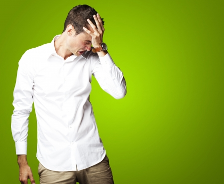 Angry young man doing frustration gesture over green background Stock Photo - 15105215