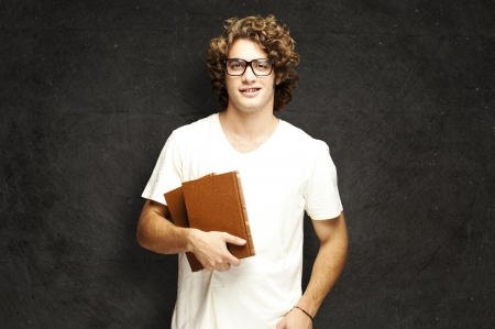 portrait of young man holding books against a grunge wall Stock Photo - 15103951