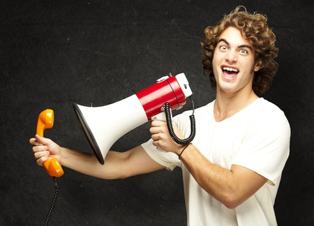 portrait of young man shouting with megaphone and talking on vintage telephone against a grunge wall photo