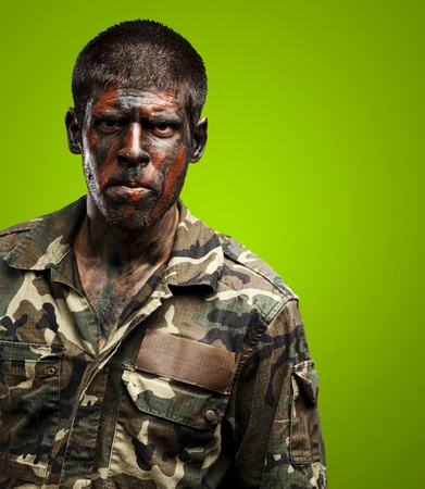 young soldier with camouflage paint looking very serious over green Stock Photo - 15104174