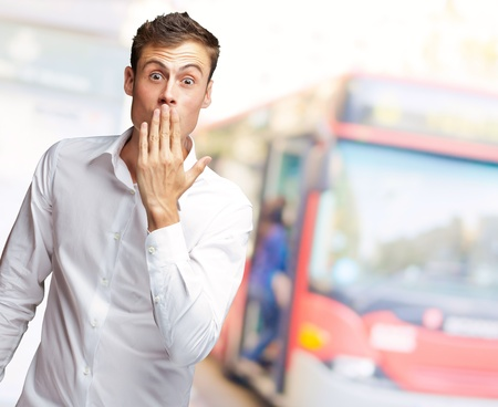 appalled: Portrait Of Young Man Covering His Mouth With Hand, Outdoor Stock Photo