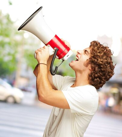 Portrait Of Young Man Shouting With A Megaphone, Outdoor photo