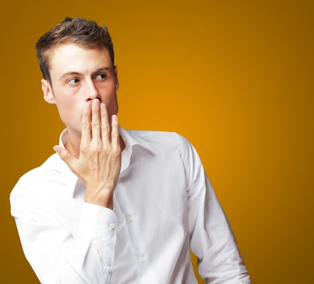 Portrait Of Young Man Covering His Mouth With Hand On Coloured Background Stock Photo - 15106613