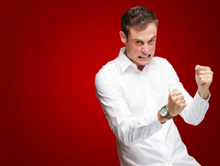 Portrait Of  Frustrated Young Man On Red Background photo