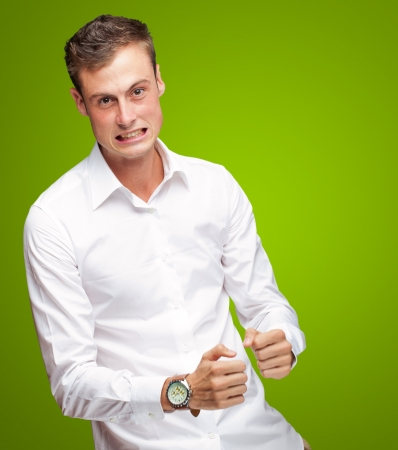 clenching fists: Portrait Of  Frustrated Young Man On Green Background Stock Photo
