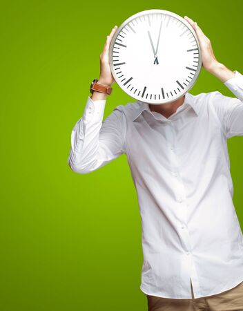 Young Man Holding Big Clock Covering His Face On Green Background photo
