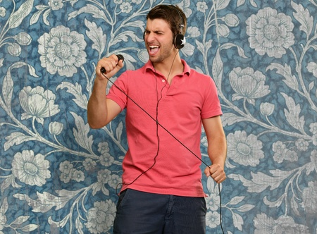 Man holding microphone in hands on wallpaper