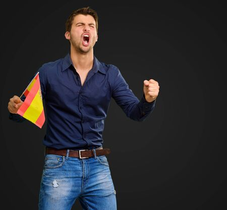 Man cheering and holding flag on black background photo