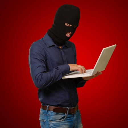 young male thief holding laptop isolated on red background Stock Photo - 15104577