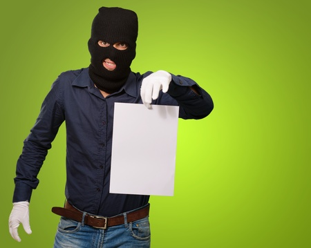 Burglar In Face Mask On Green Background Stock Photo - 15104199