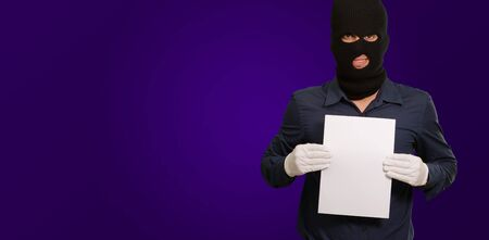 Man wearing a robber mask showing a blank paper on purple background Stock Photo - 15186992