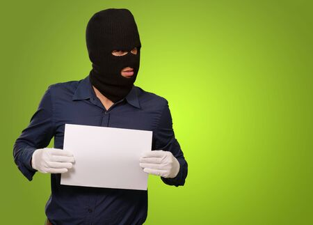 swindled: Man wearing a robber mask showing a blank paper on green background