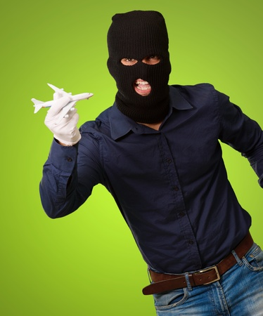 thievery: Man wearing robber mask and holding airplane miniature on green background