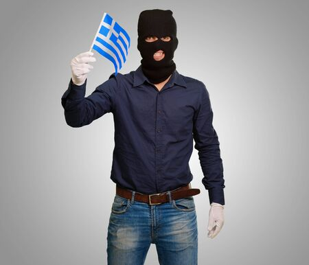Man wearing robber mask and holding flag on grey background Stock Photo - 15187421