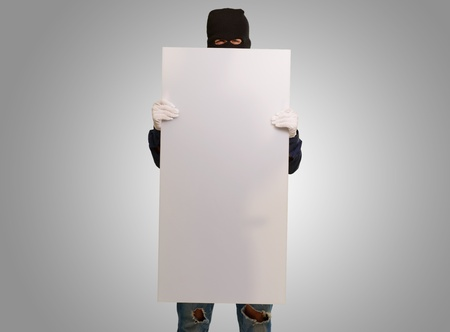 youth crime: Man wearing mask holding a blank card isolated on gray background