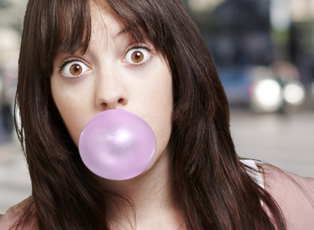 young girl with a pink bubble of chewing gum against a street background Standard-Bild