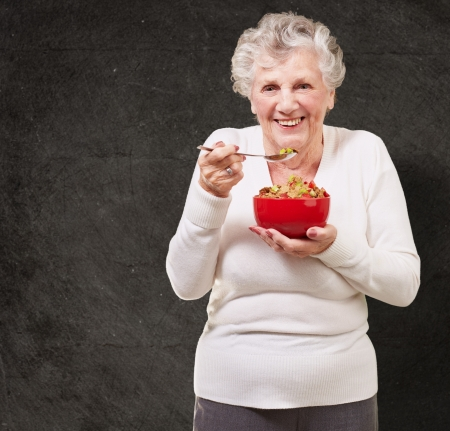 old people eating: portrait of senior woman holding a cereals bowl against a grunge wall Stock Photo