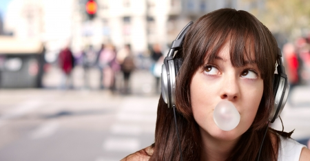portrait of young woman listening to music with bubble gum against a crowded city