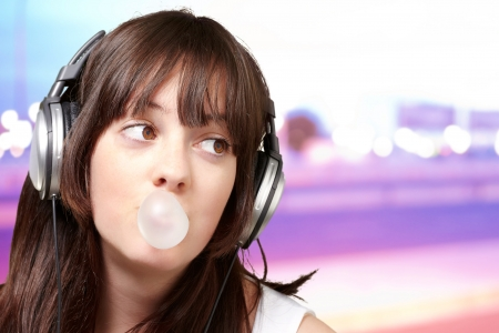 gum: portrait of young woman listening to music with bubble gum over abstract background