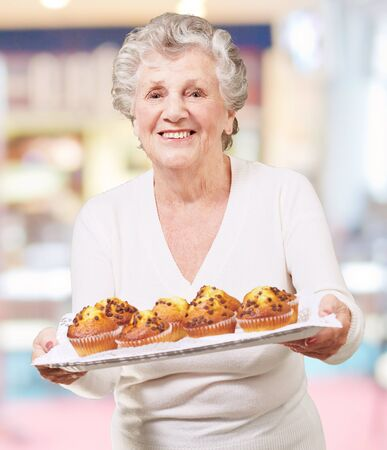 portrait of senior woman showing a chocolate muffin tray indoor photo