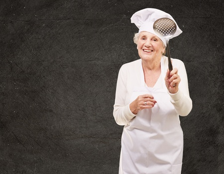 portrait of sweet senior cook woman holding a metal spoon against a grunge wall Stock Photo - 15104112
