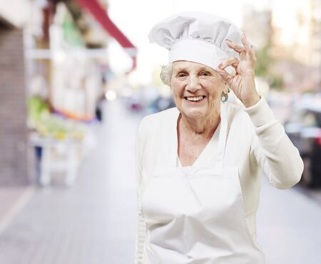 hotel worker: senior woman cook doing an excellent symbol against a street background