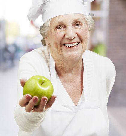 senior woman cook offering a green apple against a street background photo
