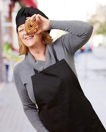 Middle aged cook woman looking through a donut at street photo