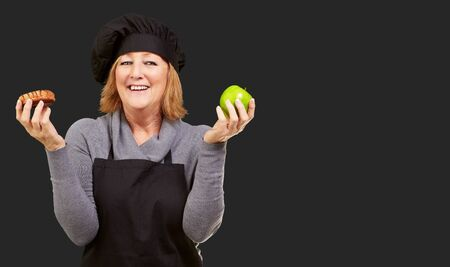 Portrait Of A Woman Holding Fruit On Black Background photo