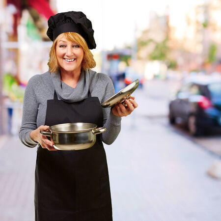 diet dinner: Middle aged cook woman holding a souce pan at street