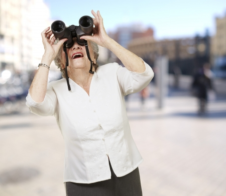 portrait of senior woman looking through a binoculars at city photo