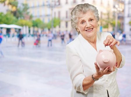 Portrait Of A Mature Woman With A Piggy Bank, Outdoor photo