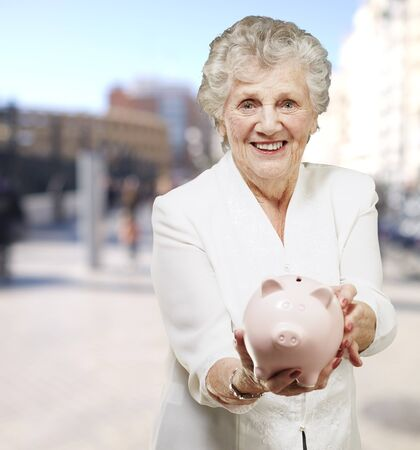 portrait of senior woman showing a piggy bank at city photo