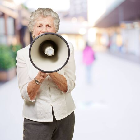 portrait of senior woman screaming with megaphone at city photo