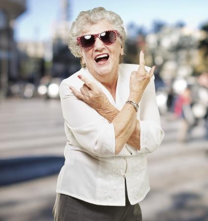 portrait of senior woman doing rock symbol at city background Stock Photo - 15104389