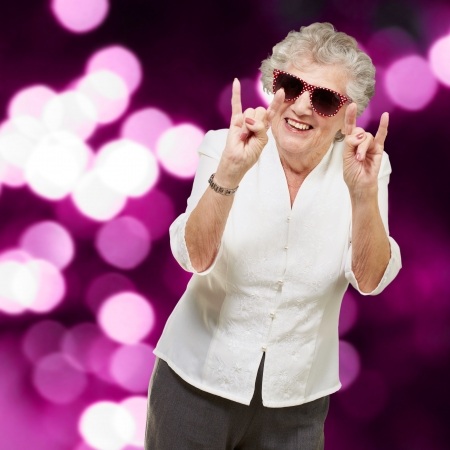 portrait of a happy senior woman doing rock symbol against a abstract purple lights background Stock Photo - 15104632