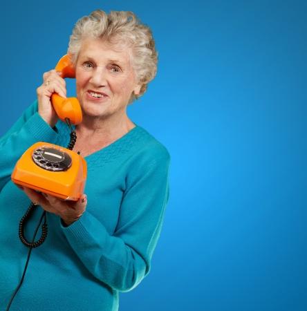 Mature Woman, Talking On Telephone On Blue Background photo