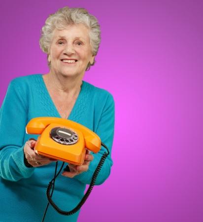 Mature Happy Woman Holding Telephone On Purple Background Stock Photo - 15104295