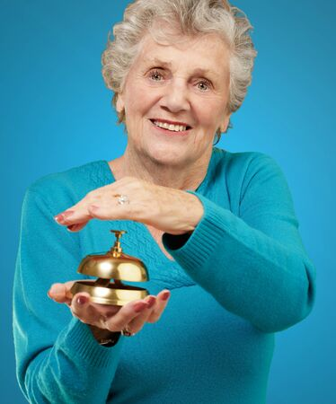 Happy Mature Woman While Holding Bell On Turquoise Background photo