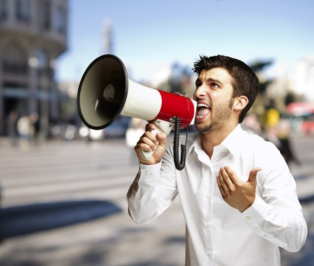 portrait of young man shouting with megaphone at street photo