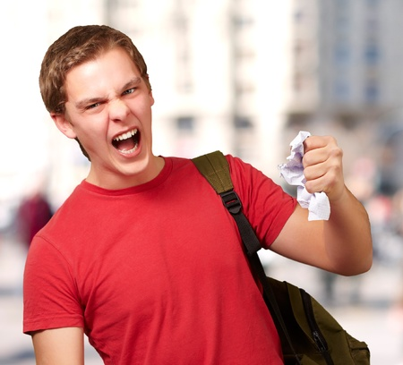 young angry student man roughing a sheet against a university Stock Photo - 15106331