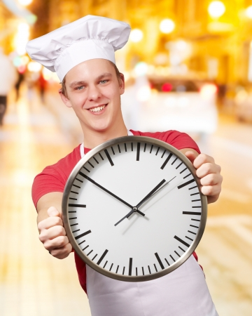 second meal: portrait of young cook man holding clock at night city Stock Photo