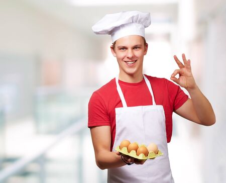 portrait of young cook man holding egg box and doing good gesture against abstract background photo