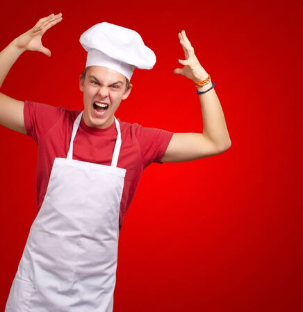 Angry Young Man Raising His Hand On Red Background photo