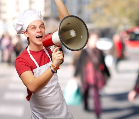 portrait of young cook man shouting with megaphone at crowded street photo