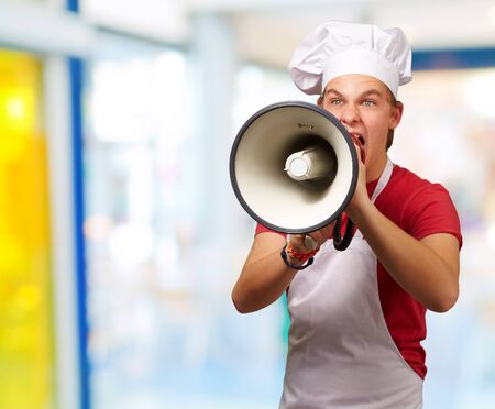 portrait of young cook man screaming with megaphone indoor photo